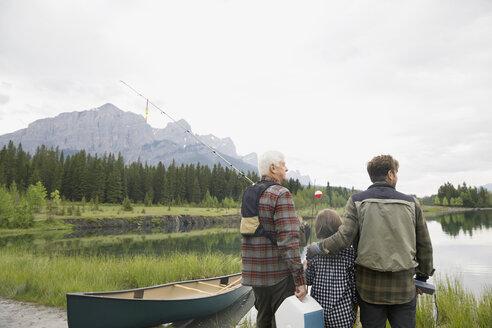 Three generations of men overlooking still lake - HEROF08104