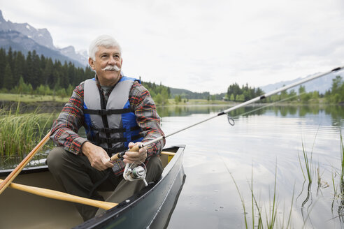 Older man fishing in canoe in still lake - HEROF08221
