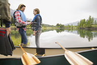 Mother and daughter in canoe by still lake - HEROF08242