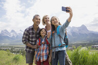 Family taking cell phone picture on rural hillside - HEROF08257