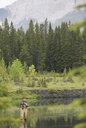 Older man fishing in still lake - HEROF08275