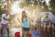 Man spraying woman with hose at car wash - HEROF08353