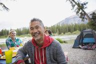Man smiling at picnic table at campsite - HEROF08365