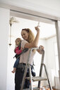 DIY mother painting trim with baby daughter in baby carrier - HEROF08428