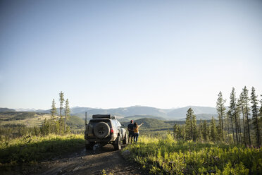 Couple enjoying overland adventure, looking at remote mountain view next to SUV, Alberta, Canada - HEROF08452