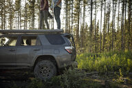 Couple enjoying overland adventure, standing on top of SUV in remote forest - HEROF08455