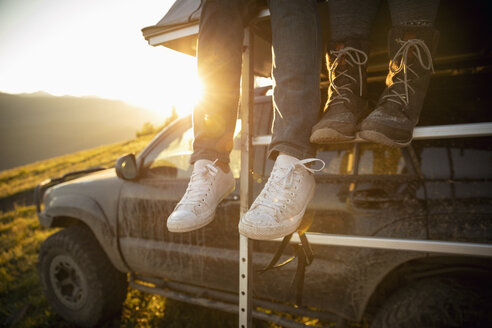 Couple dangling feet from SUV rooftop - HEROF08461
