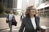 Confident senior businesswoman with coffee walking on city street - HEROF08482