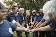 Confident volunteers joining hands in park - HEROF08488