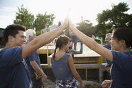 Enthusiastic volunteers high-fiving and celebrating, helping build house - HEROF08500