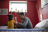 Father and son in soccer uniform celebrating with trophy on bed - HEROF08560