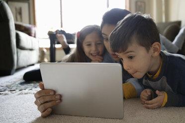 Latinx family using digital tablet on living room floor - HEROF08656