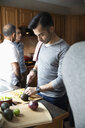 Latinx man cutting avocados in kitchen - HEROF08662