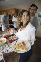 Latinx woman enjoying buffet dinner with family in kitchen - HEROF08665