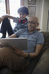 Latinx father and son using digital tablet - HEROF08671