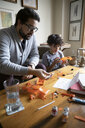 Latinx father and son assembling model car - HEROF08674