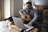 Latinx man playing guitar at laptop - HEROF08677