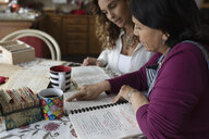 Latinx daughter and senior mother looking at recipe book in kitchen - HEROF08686