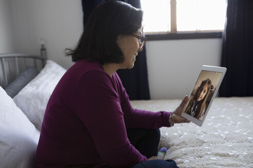 Latinx grandmother video chatting with granddaughter using digital tablet on bed - HEROF08692