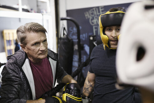 Male trainer and boxer training in gym - HEROF08707