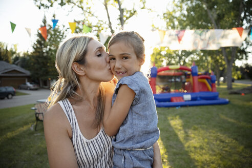 Portrait affectionate mother kissing daughter at summer neighborhood block party in park - HEROF08719
