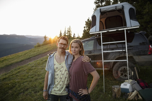 Portrait couple camping, standing by SUV with rooftop tent, Alberta, Canada - HEROF08752