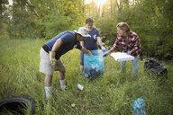 People volunteering, cleaning up garbage in woods - HEROF08791