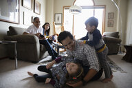 Playful Latinx father and children in living room - HEROF08881
