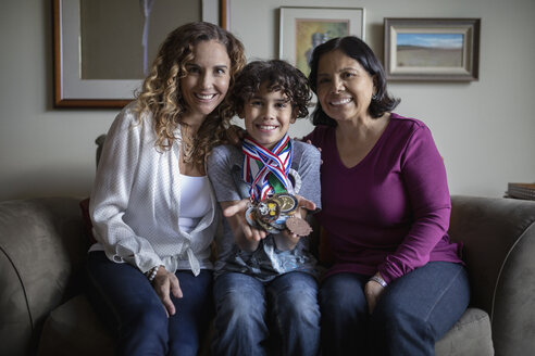 Portrait confident Latinx boy with sports medals sitting with mother and grandmother - HEROF08884