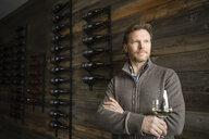 Portrait confident winemaker drinking white wine in vineyard tasting room - HEROF08905