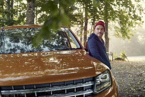 portrait mann mit roter mütze, lehnt an autotür, outdoor - PNEF01189