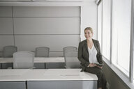 Smiling businesswoman sitting on desk in office - HEROF08910