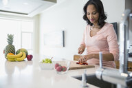 Woman slicing strawberries in kitchen - HEROF08919