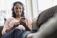 Woman listening to headphones on sofa - HEROF08934