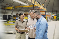 Workers examining metal parts in manufacturing plant - HEROF09024