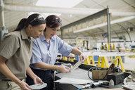 Workers examining metal part in manufacturing plant - HEROF09039