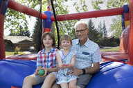 Portrait father and kids at bouncy castle in park - HEROF09126
