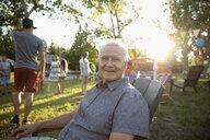 Portrait smiling, carefree senior man enjoying summer neighborhood block party in sunny park - HEROF09132