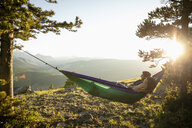 Serene couple relaxing in hammock on sunny, idyllic remote mountain hilltop, Alberta, Canada - HEROF09150