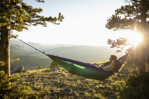 Serene couple relaxing in hammock on sunny, idyllic remote mountain hilltop, Alberta, Canada - HEROF09150