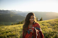 Portrait smiling young woman wrapped in blanket on sunny, idyllic mountain hillside, Alberta, Canada - HEROF09153