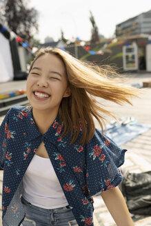 Portrait laughing, carefree teenage girl in park - HEROF09216
