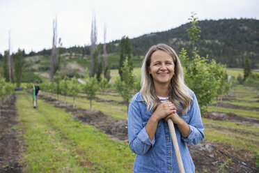 Portrait smiling, confident female farmer working in orchard - HEROF09300