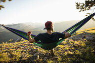 Serene man drinking coffee in sunny hammock with idyllic mountain view, Alberta, Canada - HEROF09333