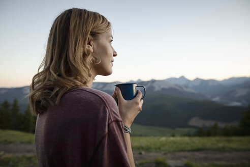 Thoughtful, serene woman drinking coffee and looking at mountain view, Alberta, Canada - HEROF09336