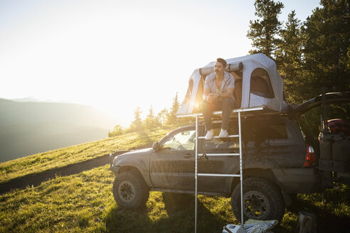 Serene man camping, relaxing at SUV rooftop tent in sunny, idyllic field, Alberta, Canada - HEROF09339