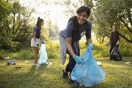 Smiling woman volunteering, cleaning up garbage in park - HEROF09363
