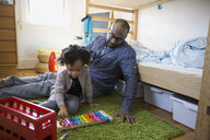 Father and daughter playing xylophone in bedroom - HEROF09504