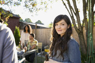 Portrait of smiling woman at backyard barbecue - HEROF09543