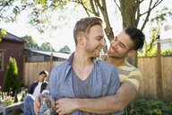 Homosexual couple hugging at backyard barbecue - HEROF09546